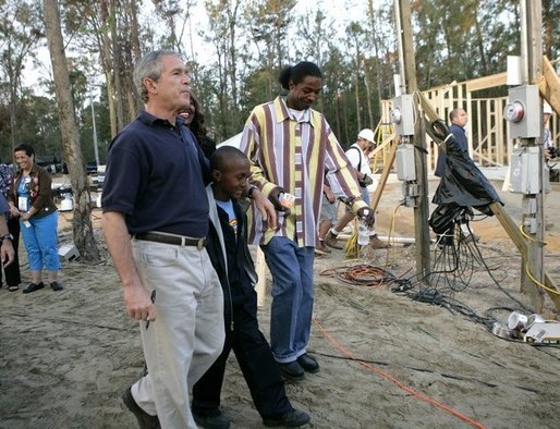 "President George W. Bush walks with members of Jackulin ""Jackie"" Collins family, Tuesday, Oct. 11, 2005, while visiting a Habitat for Humanity building site in Covington, La., where a home for the Collins family is being built, along with others for victims of Hurricane Katrina. White House photo by Eric Draper"