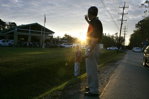 As the sun rises, President George W. Bush waves to the staff at Pine View Middle School Tuesday, Oct. 11, 2005, in Covington, La., where earlier he and Laura Bush joined a corps of Habitat for Humanity volunteers. White House photo by Eric Draper