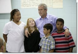 President George W. Bush spends a moment Tuesday, Oct. 11, 2005, with students at Delisle Elementary School in Pass Christian, Miss. The school reopened Tuesday for the first time since Hurricane Katrina devastated the Gulf Coast region.  White House photo by Eric Draper