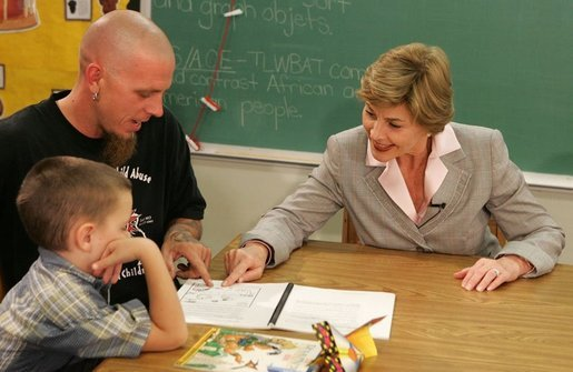 Laura Bush works with a child and father, while participating in the R.E.A.D. to Kids Training Program at J.S. Chick Elementary School in Kansas City, Mo., Tuesday, October 11, 2005. White House photo by Krisanne Johnson