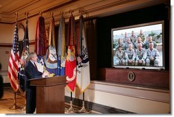 President George W. Bush gestures as he speaks with troops, from the U.S. Army's 42nd Infantry Division serving in Iraq, via video teleconference from the Eisenhower Executive Office Building in Washington, Thursday, Oct. 13, 2005.  White House photo by Paul Morse