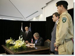 President George W. Bush signs a book of condolences, Friday, Oct. 14, 2005 at the Pakistan Embassy in Washington, to express the condolences of the American people for those who suffered as a result of the recent earthquake that struck Pakistan. Pakistan's Ambassador Jehangir Karamat is seen looking on at left. White House photo by Eric Draper