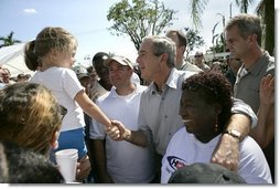 President George W. Bush greets local residents lined up at a food and water distribution center, Thursday, Oct. 27, 2005, in the hurricane damaged area of Pompano Beach, Fla.  White House photo by Eric Draper