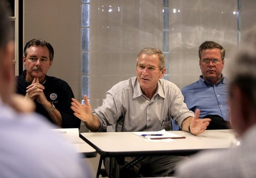 President George W. Bush addresses a meeting with local and state elected officials on hurricane damage, including FEMA Director R. David Paulison, left, and Florida Governor Jeb Bush, right, Thursday, Oct. 27, 2005, in Miami, Fla. White House photo by Eric Draper