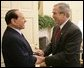 President George W. Bush welcomes Italian Prime Minister Silvio Berlusconi to the Oval Office at the White House, Monday, Oct. 31, 2005 in Washington. White House photo by Eric Draper