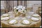 The table settings in the State Dining Room for the White House dinner Wednesday, Nov. 2, 2005, in honor of the Prince of Wales and Duchess of Cornwall. Chosen by Mrs. Laura Bush, the centerpieces are sprays of white phaeleanopsis orchids displayed in vermeil vases and compliment the Clinton China and vermeil flatware. White House photo by Shealah Craighead