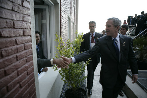 President George W. Bush reaches out for the hand of a well-wisher after participating in the 2005 class photo during opening ceremonies Friday, Nov. 4, 2005, of the Summit of the Americas in Mar del Plata, Argentina. White House photo by Eric Draper