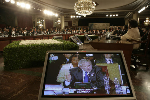 President George W. Bush and Secretary of State Condoleezza Rice are shown on a video monitor as the President speaks Friday, Nov. 4, 2005, during the opening session of the 2005 Summit of the Americas in Mar del Plata, Argentina. White House photo by Eric Draper