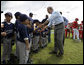 President George W. Bush greets players from the Meron's Academy Little League team in Panama City, Panama, Monday, Nov. 7, 2005. White House photo by Eric Draper