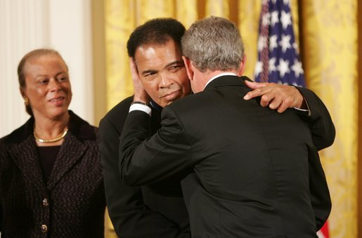 As Mrs. Lonnie Ali looks on, President George W. Bush embraces three-time heavyweight boxing champion of the world Muhammad Ali after presenting him with the Presidential Medal of Freedom Wednesday, Nov. 9, 2005, during ceremonies at the White House. White House photo by Paul Morse