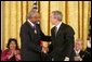 President George W. Bush presents the Presidential Medal of Freedom to baseball legend Frank Robinson in the East Room Wednesday, Nov. 9, 2005. Winning the Most Valuable Player awards in the National and American Leagues, he achieved the American League Triple Crown in 1966. Mr. Robinson became baseball's first African-American manager. White House photo by Paul Morse