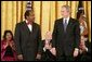 President George W. Bush exchanges a glance with Paul Rusesabagina during the presentation of the Presidential Medal of Freedom in the East Room Wednesday, Nov. 9, 2005. Paul Rusesabagina demonstrated remarkable courage and compassion in the face of genocidal terror. During the Rwandan genocide in 1994, he risked his own life to shelter more than 1,000 fellow Rwandans targeted for murder. White House photo by Paul Morse
