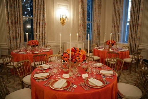 This is a view of the table settings in the State Dining Room, for the Thursday, Nov. 10, 2005 White House dinner, celebrating the National Endowment for the Arts and National Endowment for the Humanities 40th Anniversary. Chosen by Mrs. Laura Bush, the centerpieces are autumnal roses displayed in vermeil vases to compliment the Reagan China. White House photo by Paul Morse
