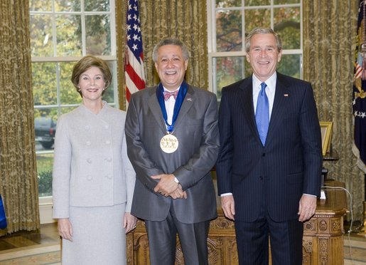 President George W. Bush and Laura Bush stand with jazz musician Paquito D'Rivera, recipient of the 2005 National Medal of Arts, in the Oval Office Thursday, Nov. 10, 2005. White House photo by Eric Draper