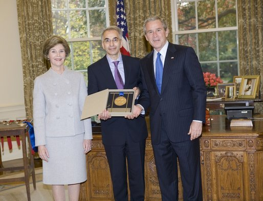 President George W. Bush and Laura Bush stand with Dereck Gillman, President of the Pennsylvania Academy of Fine Arts, who on the academy's behalf, was presented the 2005 National Medal of Arts, in the Oval Office Thursday, Nov. 10, 2005. White House photo by Eric Draper