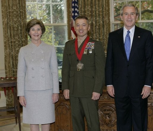 President George W. Bush and Laura Bush stand with 2005 National Humanities Medal recipient U.S. Marine Matthew Bogdanos, also an Assistant District Attorney in New York, Thursday, Nov. 10, 2005 in the Oval Office at the White House. White House photo by Eric Draper