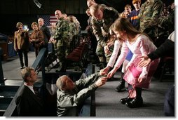 President George W. Bush reaches out to two girls after speaking Monday, Nov. 14, 2005, on the War on Terror at Elmendorf Air Force Base in Anchorage, Alaska.  White House photo by Paul Morse