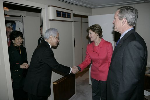 As President Bush looks on, Mrs. Laura Bush shakes hands with Japanese Ambassador to the United States Ryozo Kato and his wife, Hanayo, as the couple greeted the President and First Lady upon their arrival Tuesday, Nov. 15, 2005, to Osaka International Airport. White House photo by Eric Draper