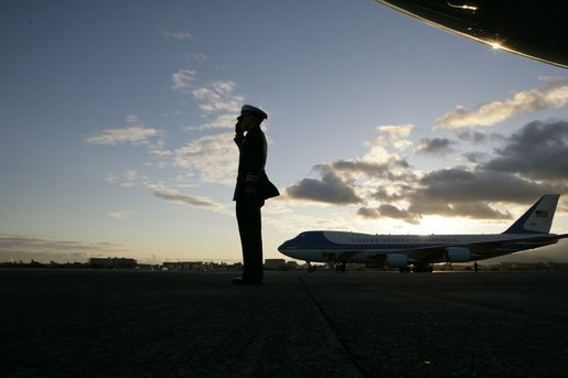 Air Force One sits on the tarmac at Osaka International Airport Wednesday, Nov. 16, 2005, as a military aide salutes the arrival of the President and Mrs. Bush. White House photo by Eric Draper