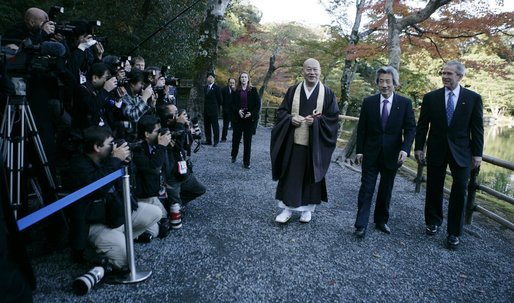 President George W. Bush and Japan's Prime Minister Junichiro Koizumi join the Reverend Raitei Arima, Chief Priest of the Golden Pavilion Kinkakuji Temple in Kyoto, as they walk past the press during a cultural visit to the temple Wednesday, Nov. 16, 2005. White House photo by Eric Draper