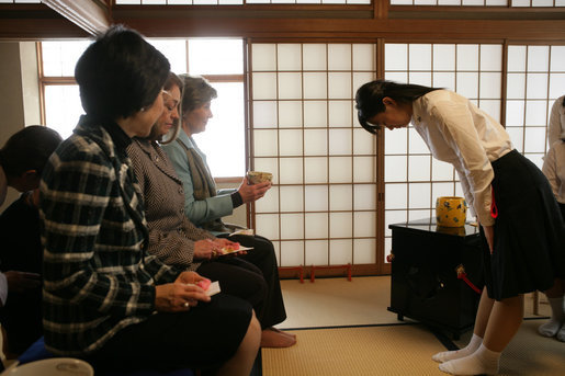 Mrs. Laura Bush accepts a cup of tea from a student in the Tea Ceremony Classroom at Doshisha Girls Junior High School and Senior High School during her visit Wednesday, Nov. 16, 2005, to Kyoto, Japan. With Mrs. Bush are Susanne Schieffer, wife of U.S. Ambassador Thomas Schieffer, and Mrs. Hanayo Kato, wife of Japanese Ambassador Ryozo Kato. White House photo by Shealah Craighead