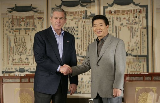 President George W. Bush and Korea President Moo Hyun Roh exchange handshakes Thursday, Nov. 17, 2005, after their meeting at the Hotel Hyundai in Gyeongju, Korea. White House photo by Eric Draper