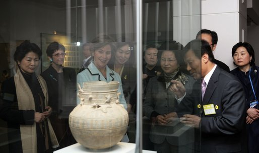 Mrs. Laura Bush looks through exhibition glass at a piece of pottery Thursday, Nov. 17, 2005, during her tour of Gyeongju National Museum in Gyeongju, Korea. With her at right is Mrs. Yang-Sook Kwon, wife of Korea President Moo Hyun Roh. White House photo by Shealah Craighead