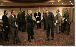 President George W. Bush and Russian President Vladimir Putin exchange handshakes Friday, Nov. 18, 2005, after their meeting in Busan, Korea, prior to the opening of the 2005 APEC conference.  White House photo by Eric Draper