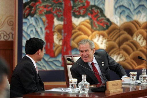 President George W. Bush and Thailand Prime Minister Thaksin Chinnawat share a laugh Friday, Nov. 18, 2005, during an opening session at the two-day, 2005 APEC summit in Busan, Korea. White House photo by Paul Morse