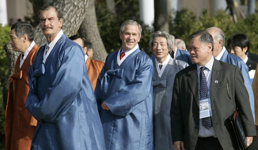 President George W. Bush peaks out behind Mexico President Vincente Fox, left, with Japan's Prime Minister Junichiro Koizumi as APEC leaders walk to the official photograph site Saturday, Nov. 19, 2005, at the Nurimaru APEC House in Busan, Korea. White House photo by Eric Draper