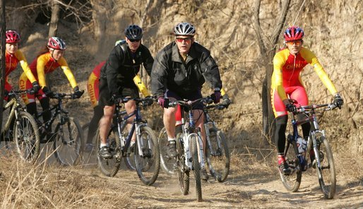 President George W. Bush leads the pack as he joins China's Mountain Biking Team for a ride Sunday afternoon, Nov. 20, 2005, in Beijing. White House photo by Paul Morse
