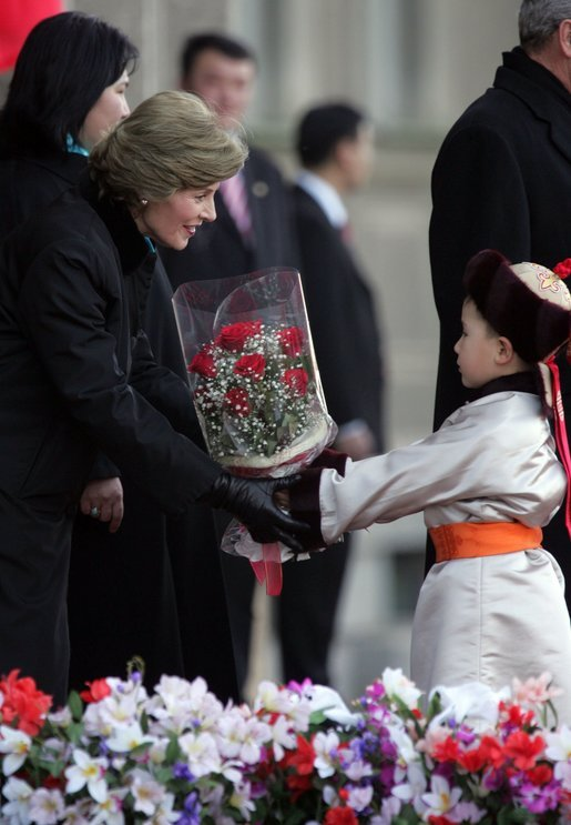 A young boy delivers a bouquet of flowers to Mrs. Bush Monday, Nov. 21, 2005, as she and President Bush joined Mongolia's President and First Lady in ceremonies in Ulaanbaatar welcoming the Bushes to Mongolia. White House photo by Paul Morse