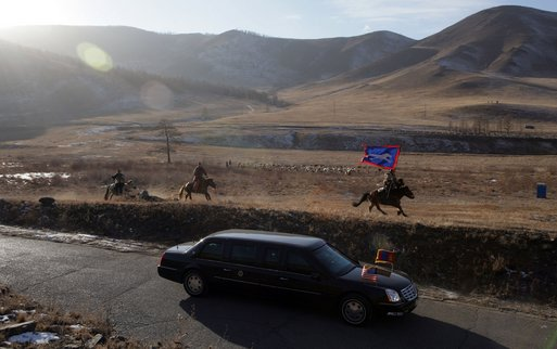 Mongolian horsemen run with the motocade carrying President George W. Bush and Mrs. Bush to a cultural event in Ikh Tenger, Mongolia Monday, Nov. 21, 2005. The stop in Mongolia was the final one for the Bushes in a 7-day visit to Asia. White House photo by Paul Morse