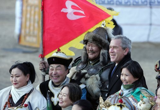 President George W. Bush poses for photos with a Mongolia horseman and other participants of a cultural event in Ikh Tenger, near the capital city of Ulaanbaatar, during a visit Monday, Nov. 21, 2005, by the President and Mrs. Bush. White House photo by Paul Morse