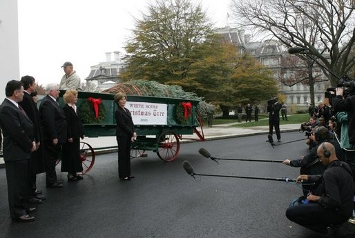 Laura Bush welcomes the arrival of the official White House Christmas tree delivered, Monday, Nov. 28, 2005, on a horse drawn wagon. This year's tree, donated by the Deal Family of Smokey Holler Tree Farm in Laurel Springs, N.C., is the 40th year the National Christmas Tree Growers Association has provided a tree to the White House. White House photo by Shealah Craighead