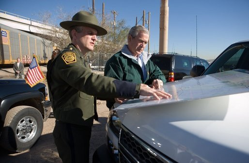 President George W. Bush looks over a map with Deputy Chief Patrol Agent Paul Besson during a tour of the El Paso Sector of the U S -Mexico border region, Tuesday, Nov. 29, 2005. White House photo by Eric Draper