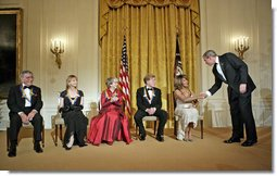 President George W. Bush congratulates Tina Turner during a reception for the Kennedy Center Honors in the East Room of the White House Sunday, Dec. 4, 2005. From left, the honorees are singer Tony Bennett, dancer Suzanne Farrell, actress Julie Harris, actor Robert Redford and singer Tina Turner. White House photo by Eric Draper