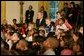 President George W. Bush and Laura Bush sit with children, Monday, Dec. 5, 2005 at the White House, as they watch a dance performance during the White House Children's Holiday Reception in the East Room. White House photo by Kimberlee Hewitt