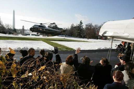 Visitors wave as President Bush takes off in Marine One from a snow-covered South Lawn Friday, Dec. 9, 2005. White House photo by Kimberlee Hewitt