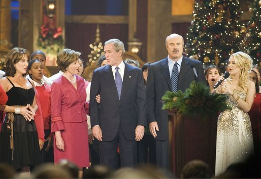 "President and Mrs. Bush sing ""Hark, the Herald Angels Sing!"" along with Dr. Phil McGraw, his wife Robin, left, and Carrie Underwood, right, during the 24th Annual Christmas in Washington at the National Building Museum in downtown Washington D.C. White House photo by Shealah Craighead"