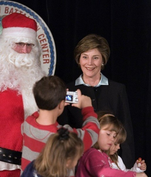 Laura Bush poses for a photo as she visits with children at the Naval and Marine Corps Reserve Center in Gulfport, Miss., Monday, Dec. 12, 2005, where she showed them a White House holiday video, 'A Very Beazley Christmas' featuring the Bush's dogs, Barney and Miss Beazley. White House photo by Shealah Craighead