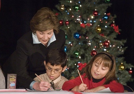"Laura Bush writes a note on a child's letter to his parent who is serving overseas, as she visits with children at the Naval and Marine Corps Reserve Center in Gulfport, Miss., Monday, Dec. 12, 2005, showing them a White House holiday video featuring the Bush's dogs ""Barney and Miss Beazley."" White House photo by Shealah Craighead"