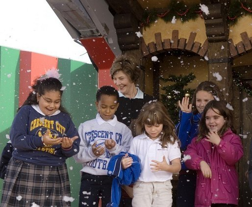 Laura Bush and children from New Orleans neighborhoods react to a downpour of fake snow flakes, Monday Dec. 12, 2005 at the Celebration Church in Metairie, La., during a Toys for Tots event. White House photo by Shealah Craighead