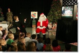 Laura Bush visits with children at the Naval and Marine Corps Reserve Center in Gulfport, Miss., Monday, Dec. 12, 2005, showing them the White House holiday video, 'A Very Beazley Christmas' featuring the Bush's dogs, Barney and Miss Beazley. White House photo by Shealah Craighead