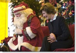 Laura Bush talks with children from New Orleans neighborhoods as she sits with Santa Claus, Monday Dec. 12, 2005 at the Celebration Church in Metairie, La., during a Toys for Tots event.  White House photo by Shealah Craighead