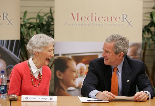 President George W. Bush smiles at 85-year-old Eloise Cartwright as he joins the residents of Greenspring Village Retirement Community and others for a roundtable discussion on the Medicare Prescription Drug Benefit Tuesday, Dec. 13, 2005, in Springfield, Va. White House photo by Paul Morse