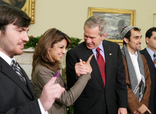 "President George W. Bush stands with out-of-country Iraqi voters Thursday in the Oval Office of the White House. The President told the media later, ""I was struck by how joyous they were to be able to vote for a government -- a permanent government under a new constitution."" White House photo by Paul Morse"