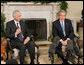 President George W. Bush is joined by Samir Sumaidaie, Iraq Ambassador to the United Nations, in the Oval Office Friday, Dec. 16, 2005. The Ambassador holds up his finger, dyed purple to signify his vote yesterday in his country's parliamentary elections. White House photo by Paul Morse