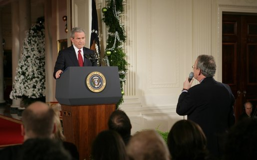 "President George W. Bush listens as Terrence Hunt of The Associated Press delivers a question Monday, Dec. 19, 2005, during the President's press conference in the East Room of the White House. In response to Mr. Hunt's question, the President responded, ""We're at war, and we must protect America's secrets."" White House photo by Paul Morse"