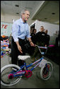 "President George W. Bush helps guide a donated bicycle to a toy distribition vehicle, Monday, Dec. 19, 2005, at the ""Toys for Tots"" collection center at the Naval District Washington Anacostia Annex in Washington, D.C. White House photo by Kimberlee Hewitt"